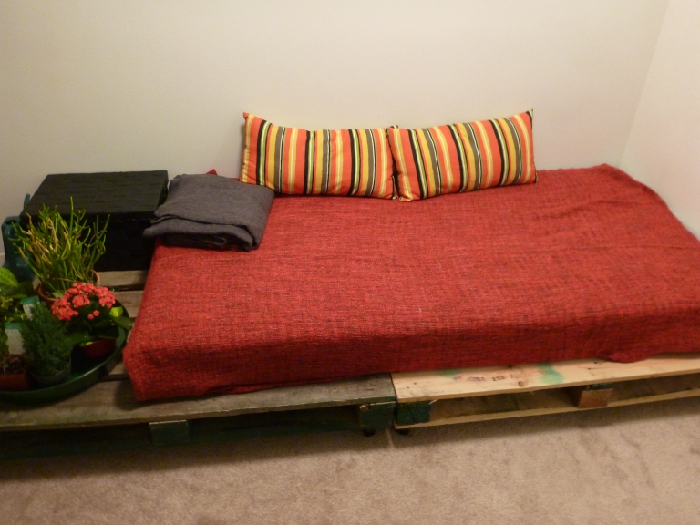 A couple of old wooden pallets can be easily transformed into a cosy daybed.